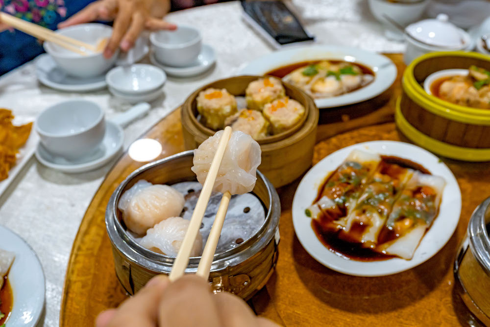 People using chopsticks and having Hong Kong dimsum in restaurant